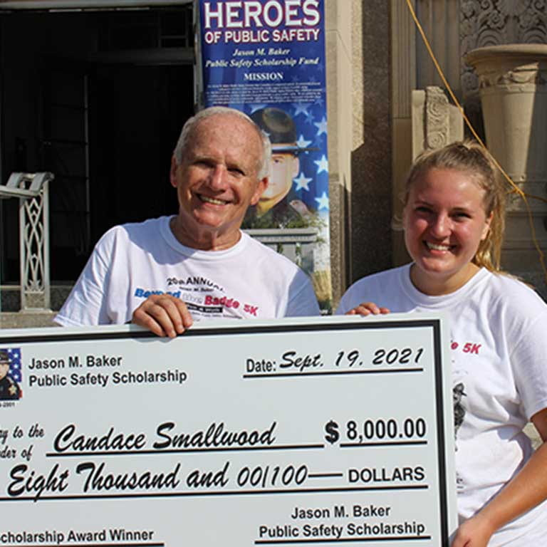 A woman and man stand in white tshirts holding large scholarship check