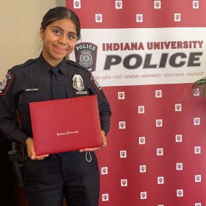woman standing in police uniform holding diploma in front of IU Police Department backdrop