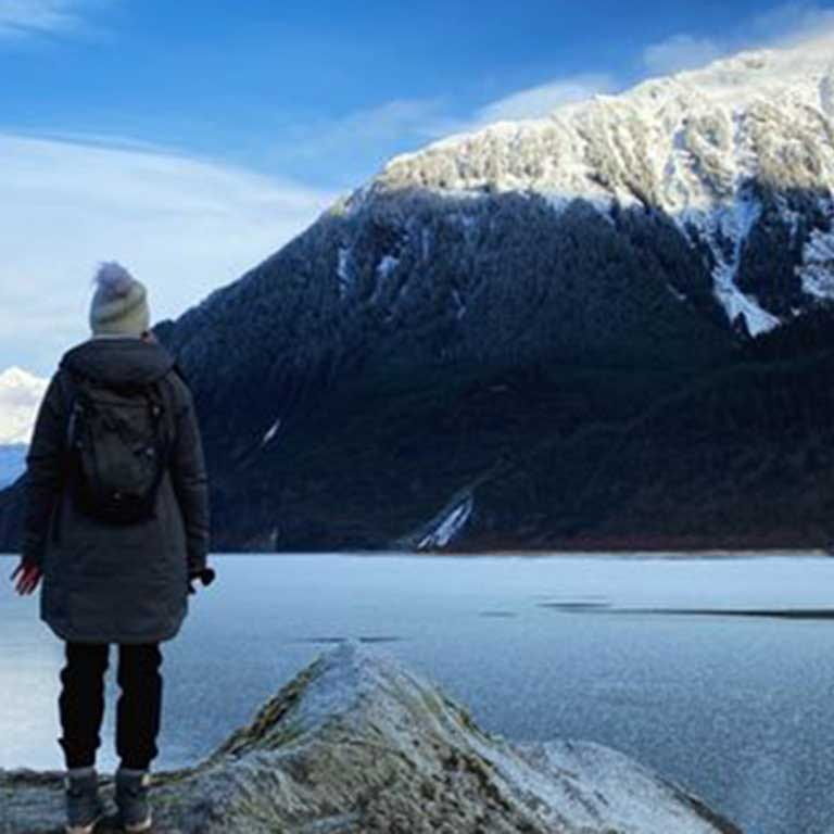 woman stands with back to camera facing snowcapped mountain by frozen lake