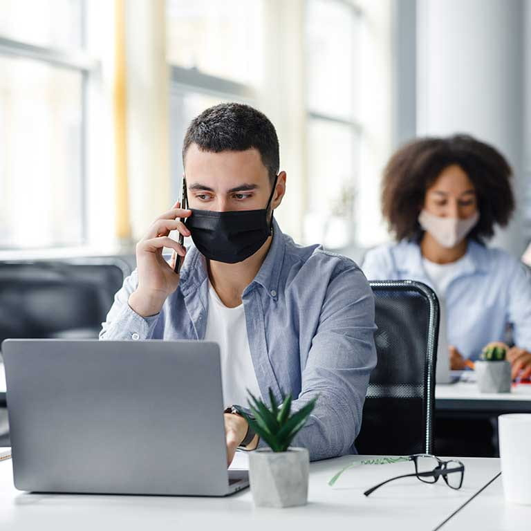 Photo of three people wearing masks in an office typing on laptops