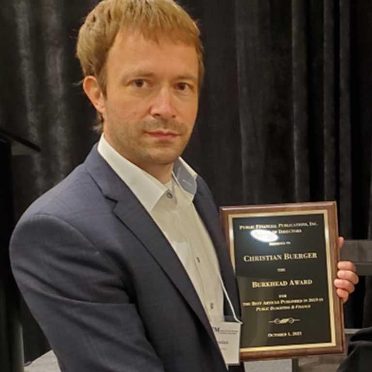 man holding award plaque
