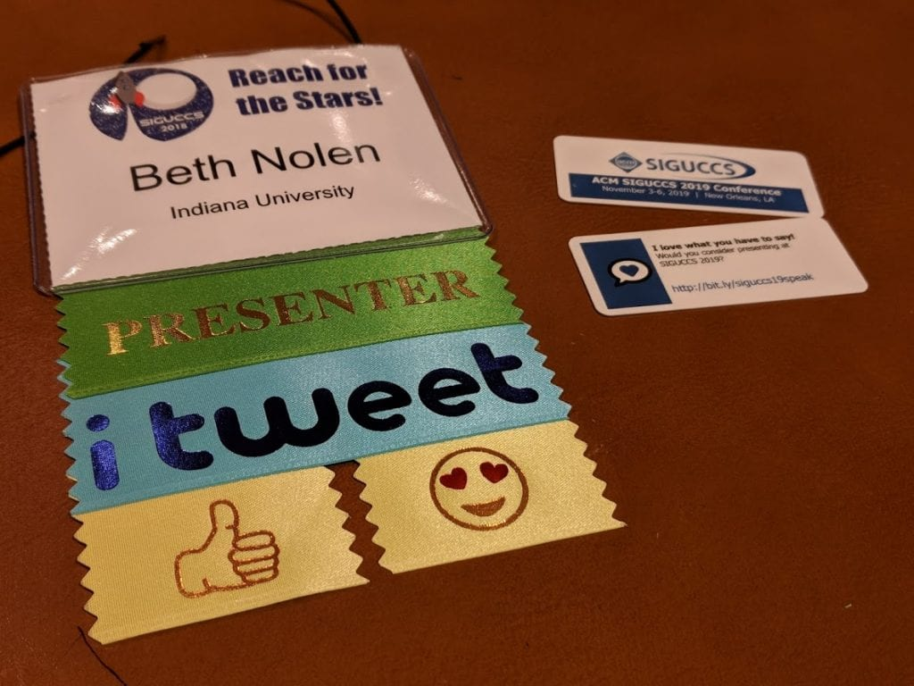 "My conference badge, with ribbons attached that say ""Presenter"" and ""i tweet"", as well as two emoji ribbons, one with a thumbs up and one with a smiley with heart eyes.  There are also two miniature business cards next to the badge, with information about next year's conference on them."