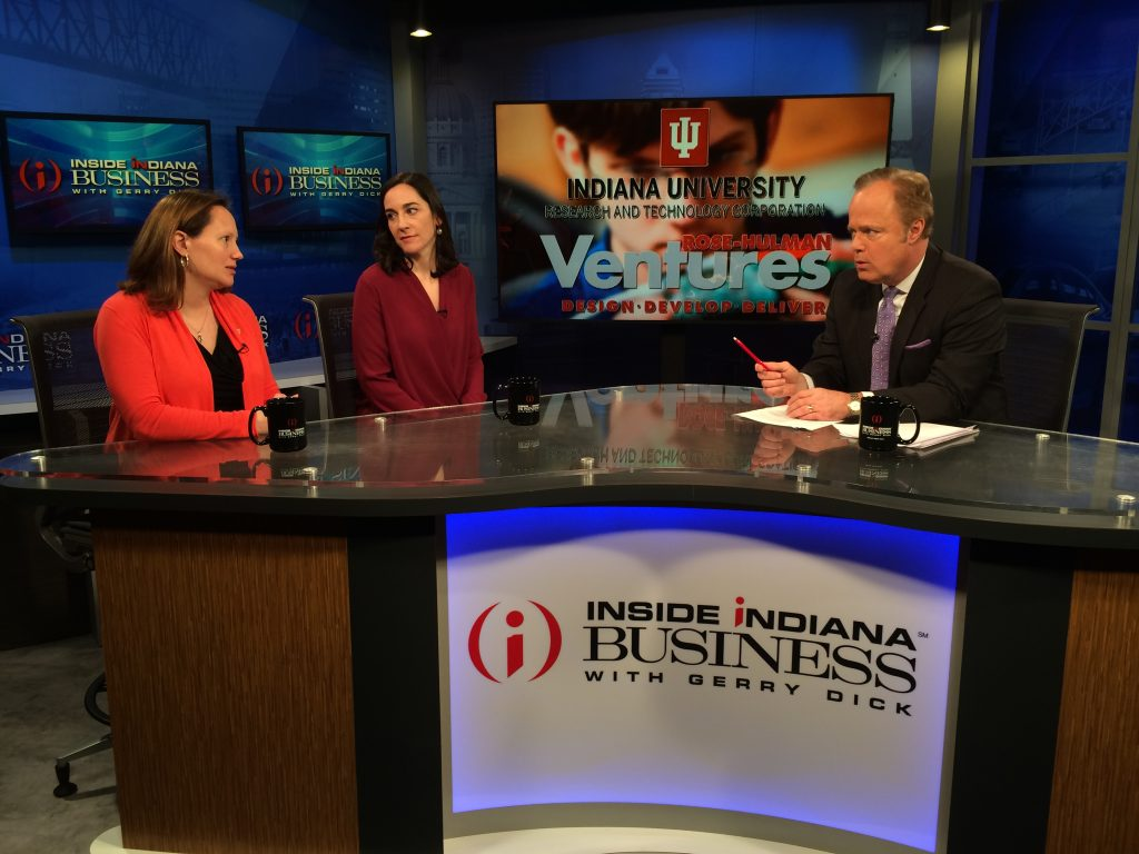 "Jennifer Finefield (IURTC) and Elizabeth Hagerman (Rose-Hulman Ventures) sit on one side of a curved desk branded ""Inside Indiana Business"" across from Gerry Dick, the show's host."