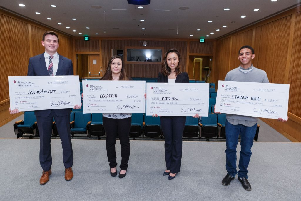 Four students, two women and two men, stand shoulder to shoulder, holding oversized checks. The students were named winners of the 2017 JagStart Business Pitch competition held at IUPUI.