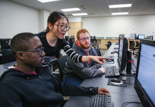 Two male students in a computer laboratory watch a female teacher point at a computer screen.