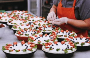 Person in apron prepares dessert dishes.