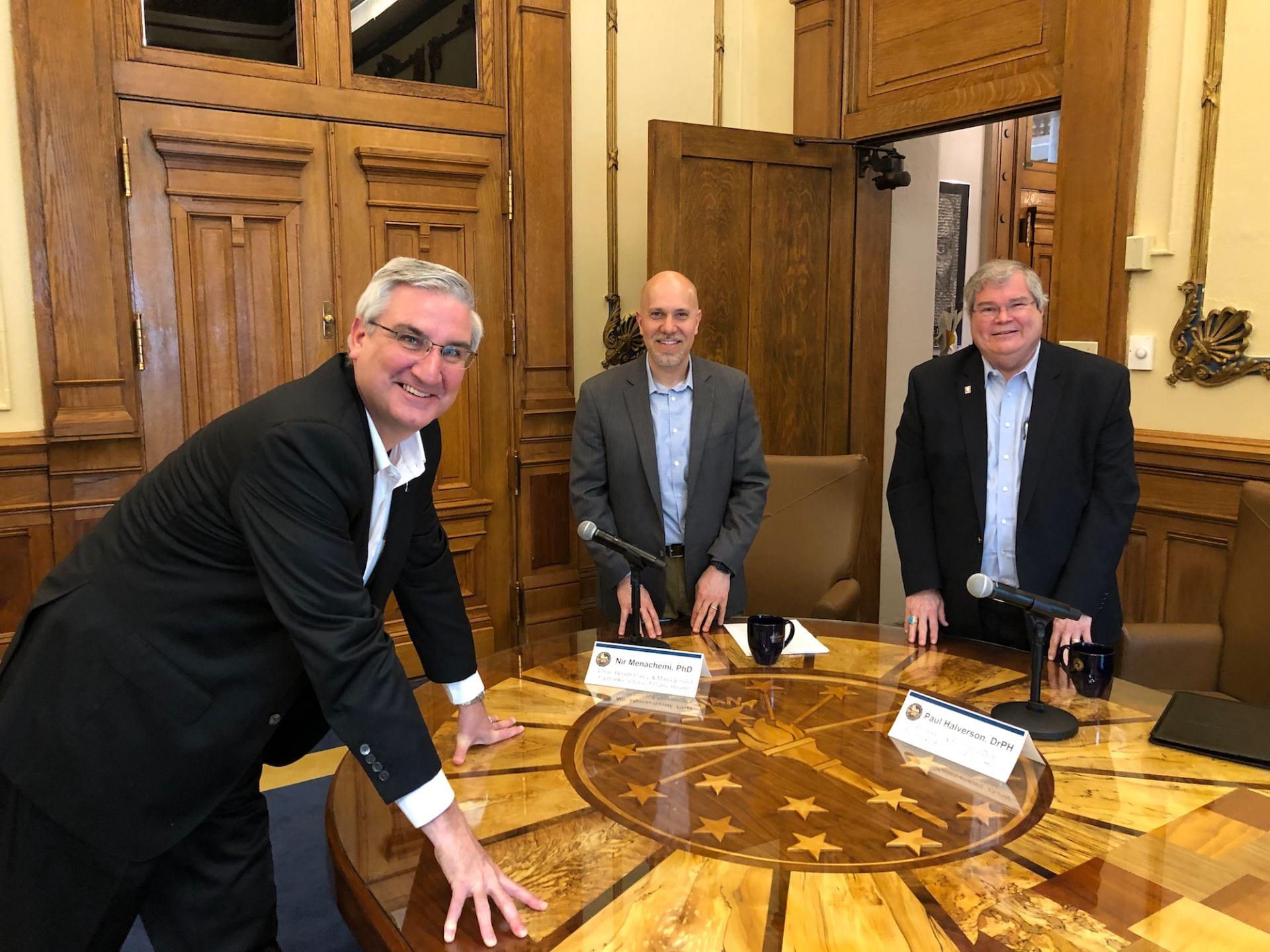 Dean Halverson, Dr. Nir Menachem and Gov. Eric Holcomb gather around board table.