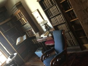 A picture of Theophilus Wylie's Library showing three bookcases with antique books, a desk, bookstand, and a rocking chair.