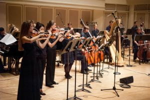 Performance in Auer Hall featuring row of violins, cellos and a harp.