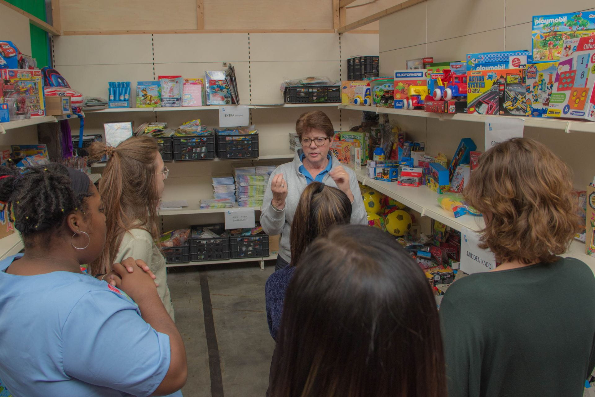 A volunteer at Jarige Job discusses how to pack a birthday box for a local child.