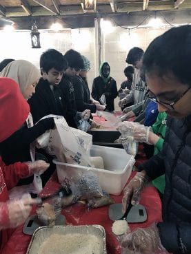 Islamic Community Center of Potomac Hunger Van volunteers make sealed lentil quinoa casserole meals in collaboration with the National Hunger Van program in Potomac, MD. Photo by Fatimah Bromund