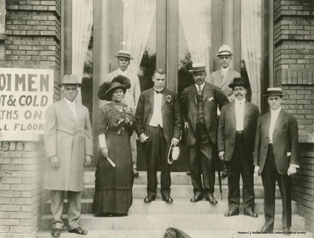 Madam C.J. Walker (second from left) stands next to fundraiser, philanthropist, and educator Booker T. Washington (holding hat in hand).