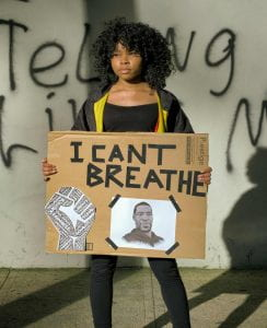 """young Black woman holding cardboard sign saying """"I can't breathe."""""""