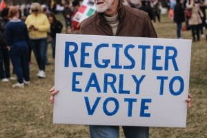 "Man holding a sign that says, ""Register Early to Vote."""
