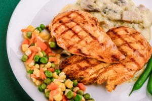 This photo is of a dinner plate with baked chicken breasts and mixed vegetables.