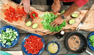 Photo shows dishes of colorful food and a pair of hands chopping lettuce.
