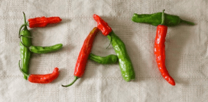 The word EAT is spelled out with red and green peppers.