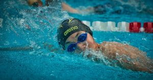 Thephotoshows a young woman wearing goggles and a swim cap doing laps in a swimming pool.
