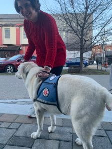 The photo shows Adria and her service dog Lucy outside on a sidewalk.
