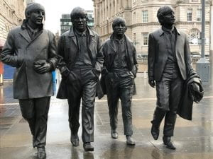 Life-sized bronze statues of The Beatles walking down a sidewalk.
