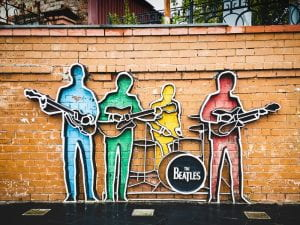 Photo shows metal art on a brick wall displaying the four Beatles with their instruments.