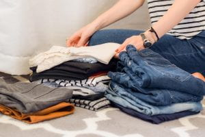 Photo shows a young woman folding laundry.