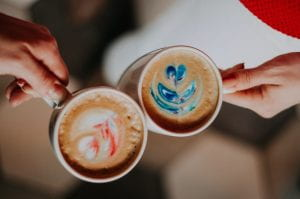 two cups of coffee touching each other as if making a toast