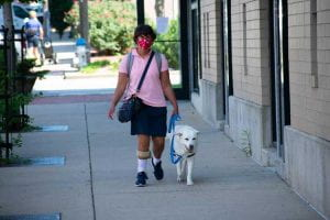 Adria walks with Lucy on a sidewalk.
