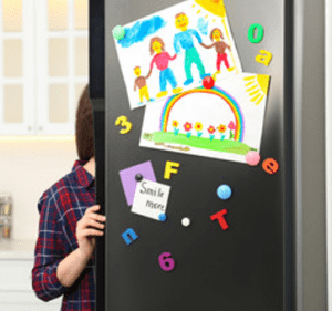 A woman opening a refrigerator that has a child's artwork posted on the door.