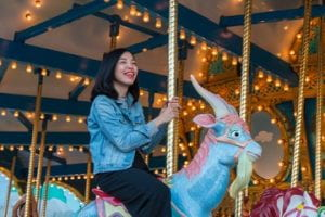 young girl riding a unicorn on a merry-go-round.