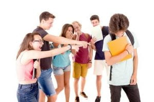 a smalll group of teens laughing and pointing at a boy with his head turned down