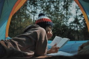 Girl reading in a tent