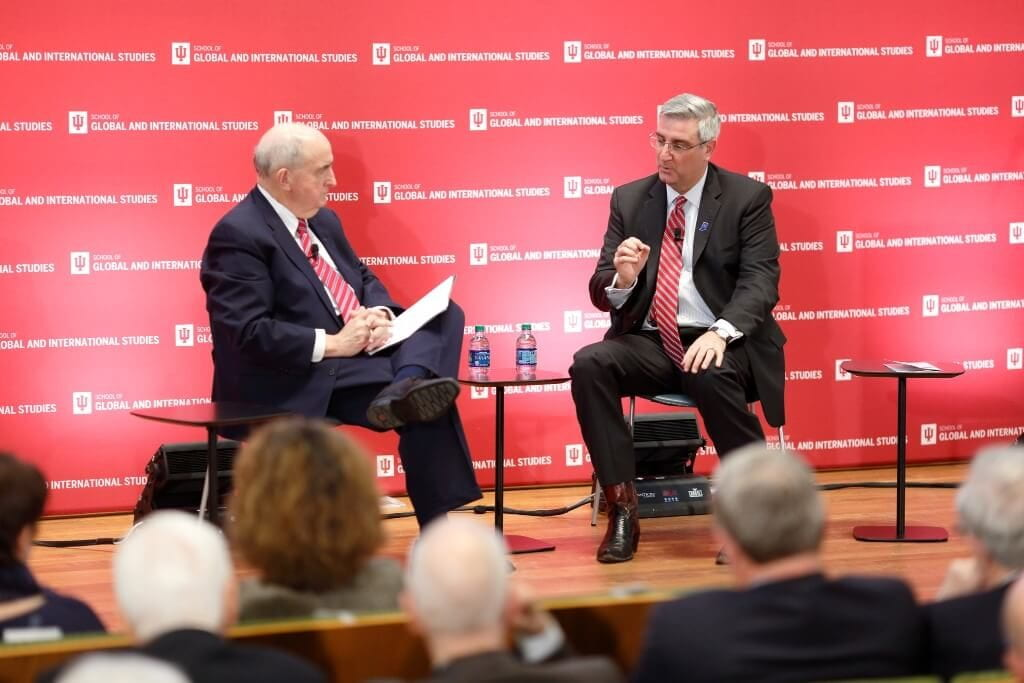IU President Michael A. McRobbie, left, sits on stage with Indiana Gov. Eric Holcomb.