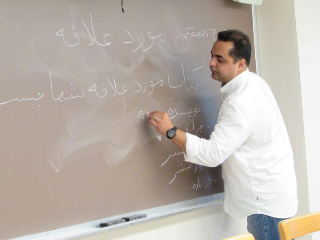 Professor writing on blackboard.