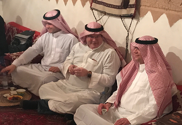 Roy Hooper, Paul Halverson, and David Russomanno don traditional Saudi attire for men and prepare for a traditional Saudi meal.