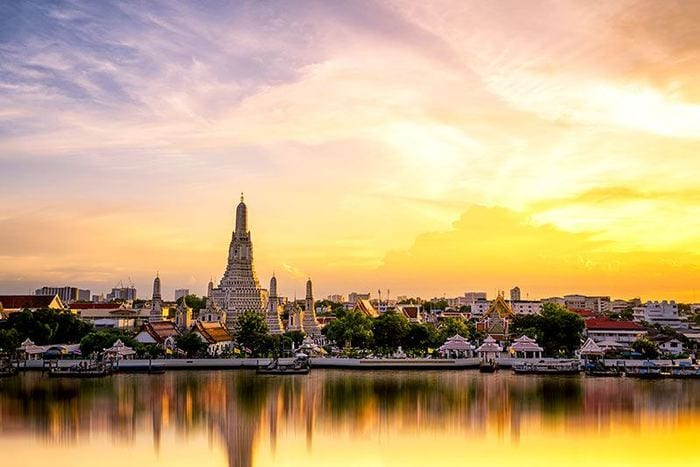 A temple and other buildings alongside a river in Bangkok