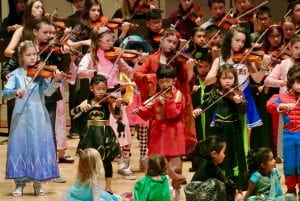 Young violinists dressed in Halloween costumes performing.