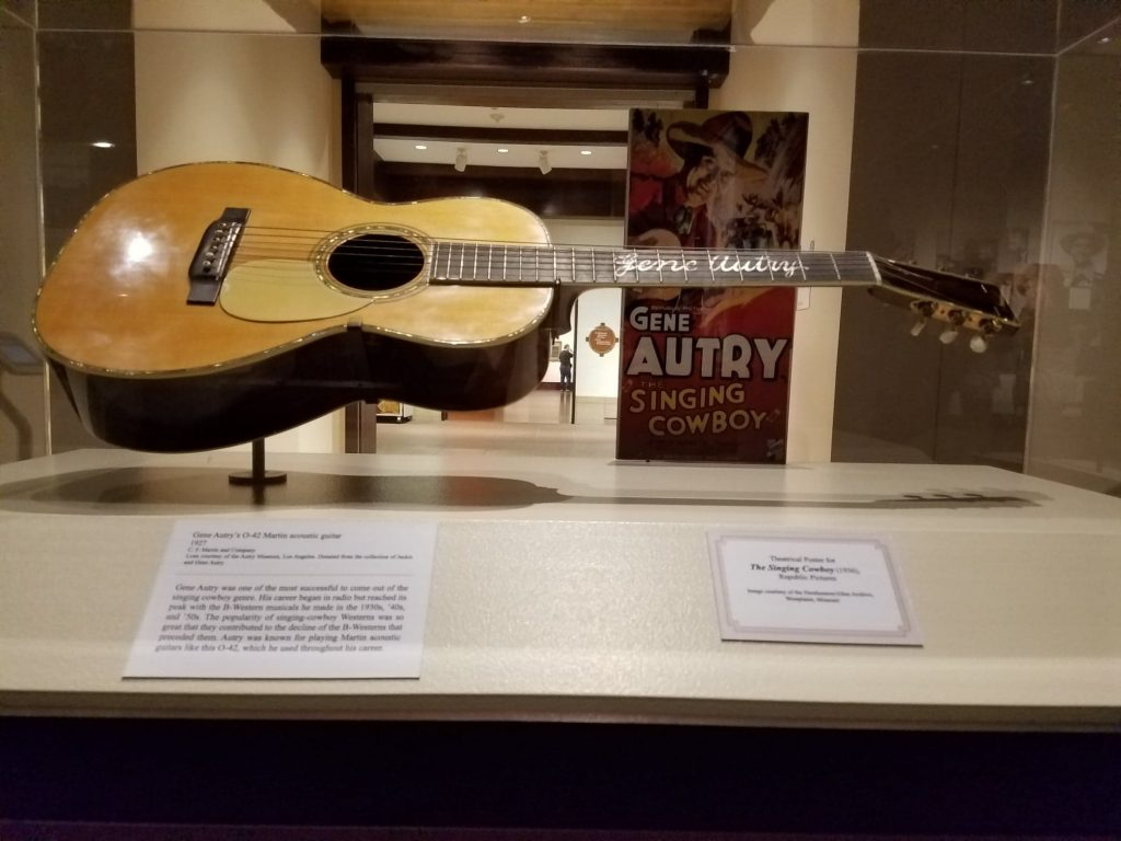One of Gene Autry's guitars and a poster forThe Singing Cowboy (1936)