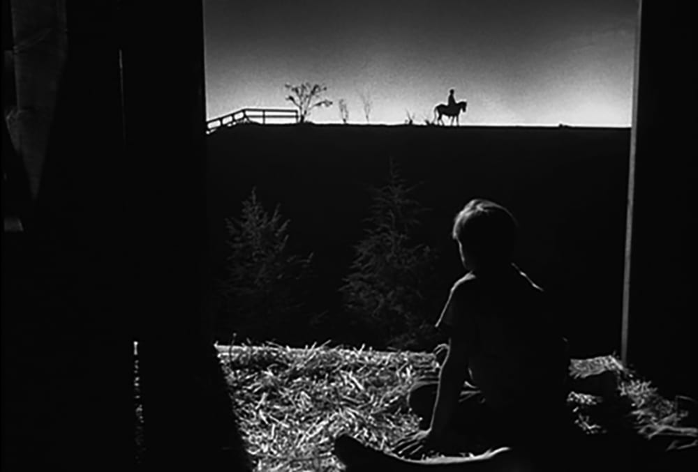 Billy Chapin watches a distant figure in The Night of the Hunter (1955)