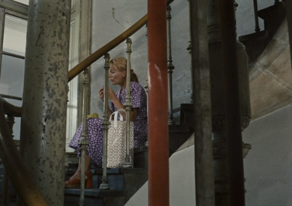 By the end of the film, Yolanda, a new coworker from Yugoslavia, has literally taken Emmi's place, by replacing her position alone on the stairs shown earlier in the film.