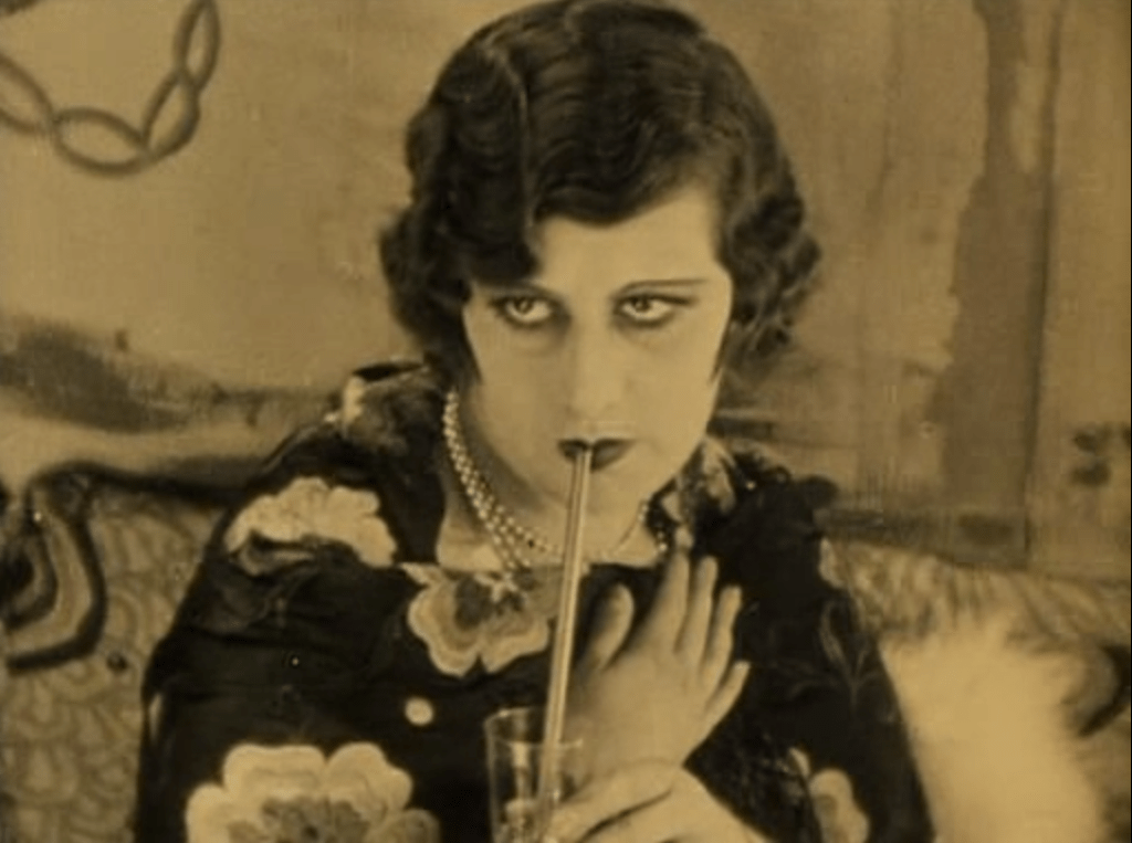 woman drinking a cocktail, looking up with desire