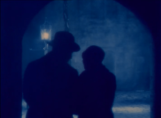 blue-tinted screenshot of silhouetted couple walking toward a street lamp
