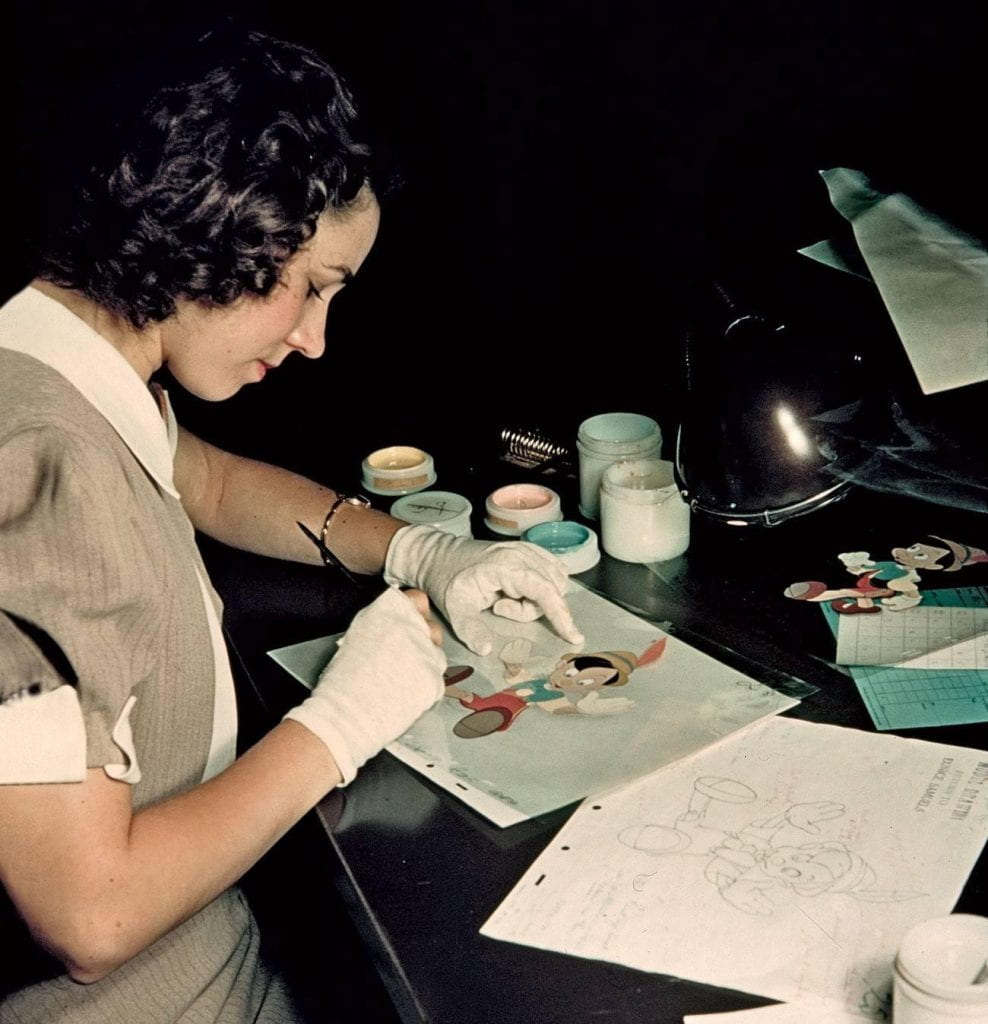 A woman in the Ink and Paint Department colors in a cel for Pinocchio