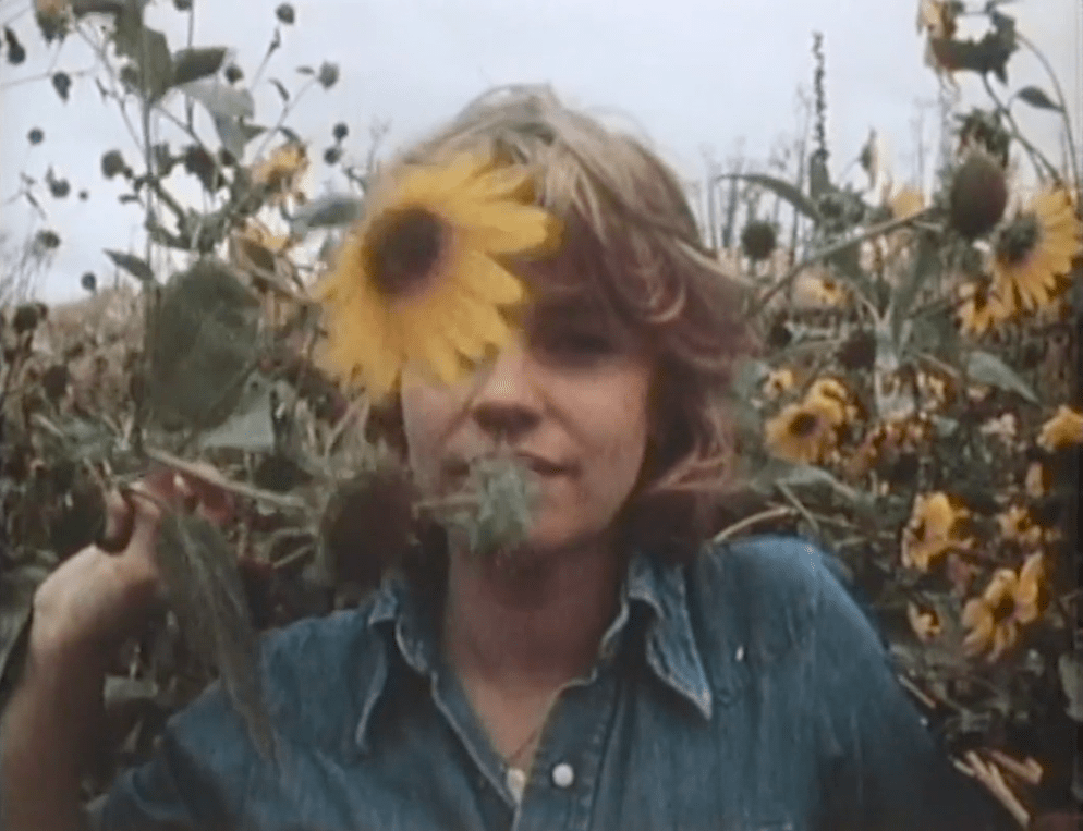 screenshot from Slow Moves of Julie in the midst of a sunflower field, pulling a flower in front of her face