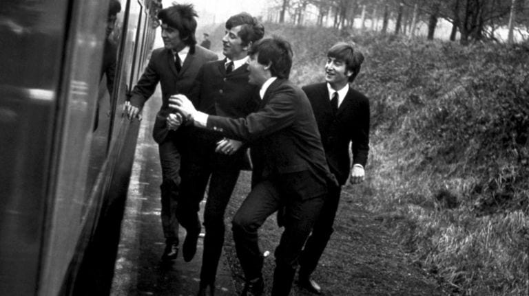 The Beatles harassing a man while running alongside a train.