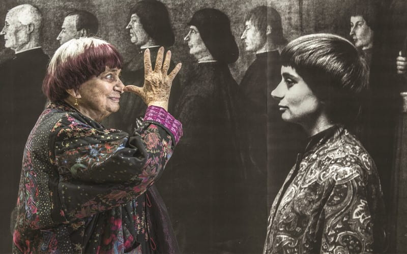 Agnès playfully posing with a younger photo of herself