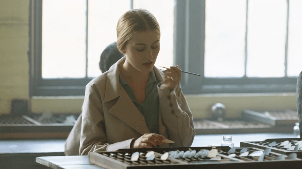 A blonde woman wearing a work smock puts a thin paintbrush to her mouth