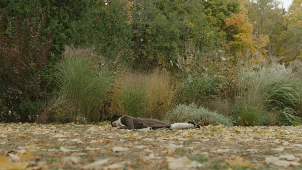 wide shot of Josephine lying face down, alone, in a clearing