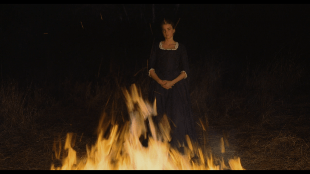 Héloïse stands before a bonfire, almost appearing as if she's in it