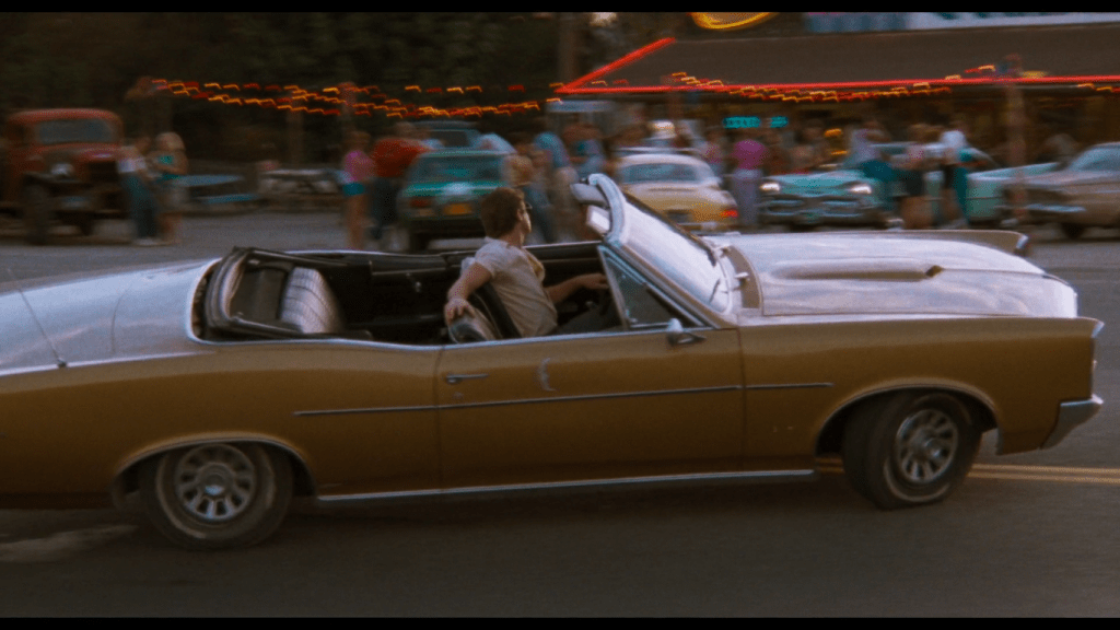 a man in a gold convertable pulls into a diner parking lot